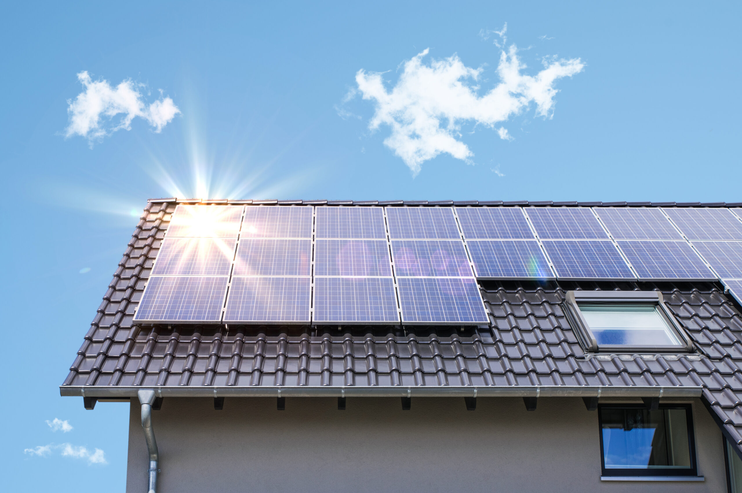 Instalacja fotowoltaiczna zainstalowana na dachu. Promienie słońca odbijają się od paneli fotowoltaicznych.