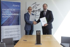 Dwóch mężczyzn stojących, podających sobie dłonie, trzymających umowy partnerskie między firmami Mazdą i Alians OZE.